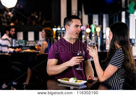 Couple having an aperitif with wine in a bar