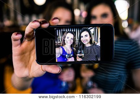 Happy brunettes taking selfie with white wine in a bar