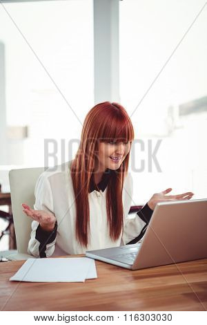 Confused hipster businesswoman using her laptop in office