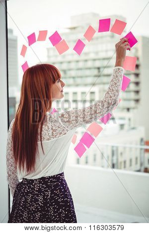 Rear view of a hipster woman doing a heart in post-it in office
