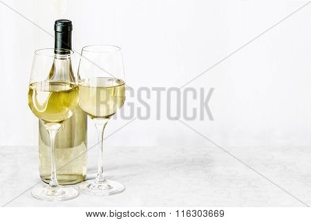 Bottle Of Vine And Two Glass Wine Are Stand On The White Tablecloth