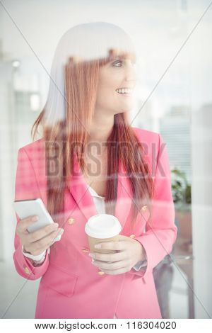 Hipster businesswoman texting with her smartphone in office