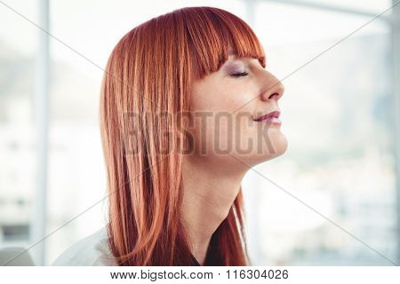 Side view of a hipster businesswoman in office
