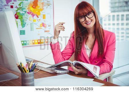 Smiling hipster businesswoman at her desk in office