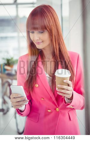 Hipster businesswoman holding coffee cup and smartphone in office