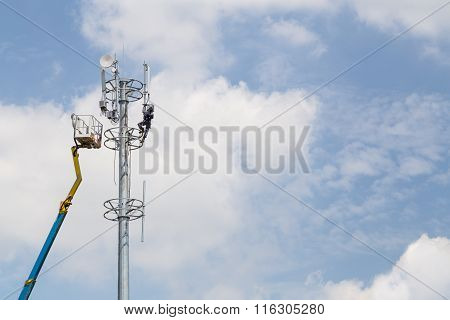 Worker Installing Antenna On Tall Telecommunication Tower With Crane