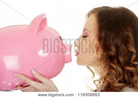 Business woman kissing a piggybank.