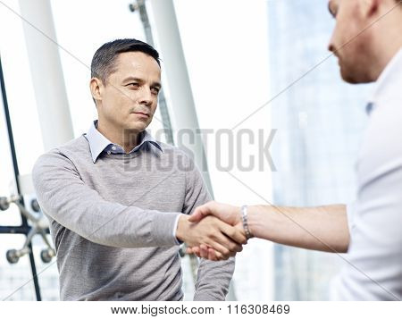 Businessman Shaking Hands With Competitor