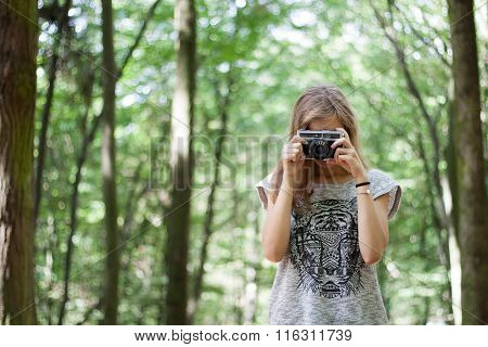 Young girl in casual clothes with old retro vintage camera photographing in forest. Brown hair, long