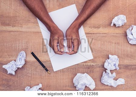 Overhead view of businessman making paper balls at desk in office
