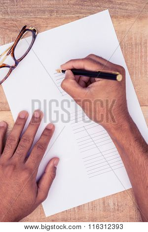 High angle view of businessman writing on paper at desk in office