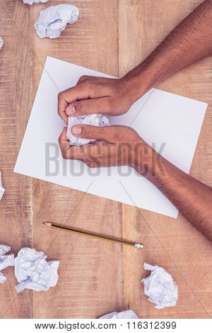 Overhead view of businessman by notepad making paper balls at desk in office