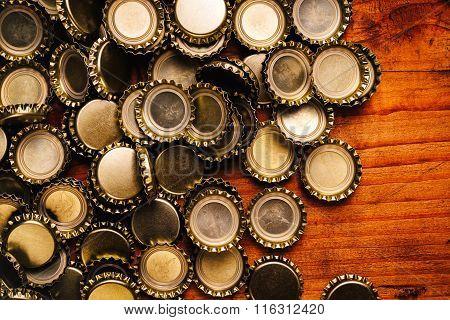 Large Pile Of Beer Bottle Caps On Wooden Desk