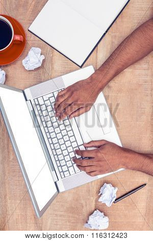 Overhead of stressed businessman using laptop at desk in office
