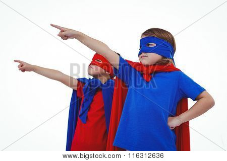Masked kids pointing somewhere pretending to be superheroes on white screen