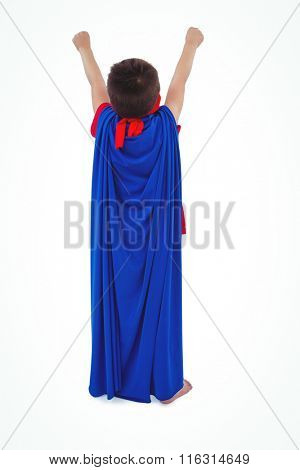 Rear view of masked boy raising fists pretending to be superhero on white screen
