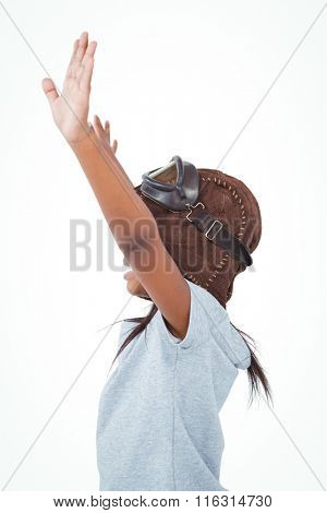 Side view of girl with outstretched arms pretending to be pilot on white screen