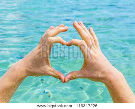 hand of boy forms a heart with the ocean as background