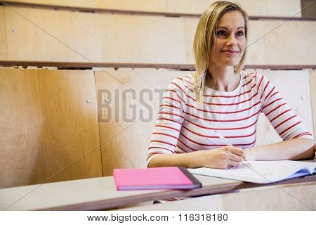 Happy female student looking away at the university