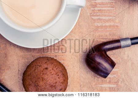 Close-up of coffee with muffin and smoking pipe on table