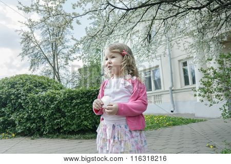 Outdoor springtime reverie portrait of little curly blonde at flowering fruit tree and porch backgro