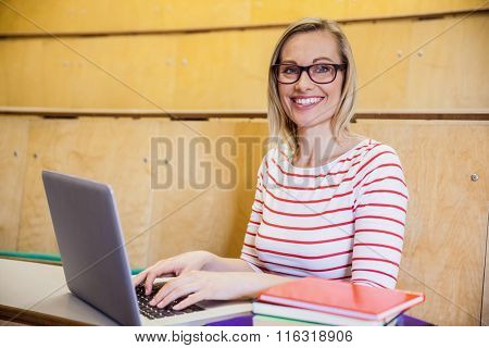 Happy female student typing on laptop at the university