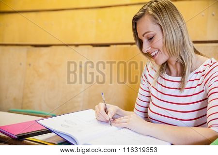 happy female student writing notes at the university