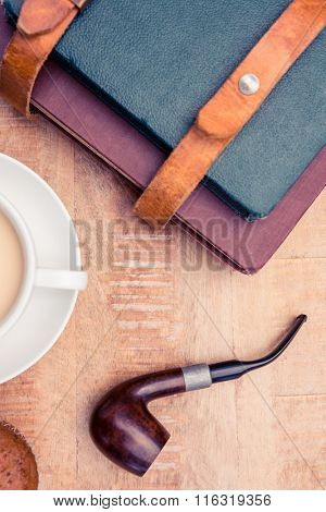 Close-up of coffee with diaries and smoking pipe on table