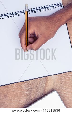 Cropped image of businessman writing on book at desk