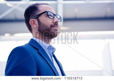 Confident businessman standing in brightly lit office