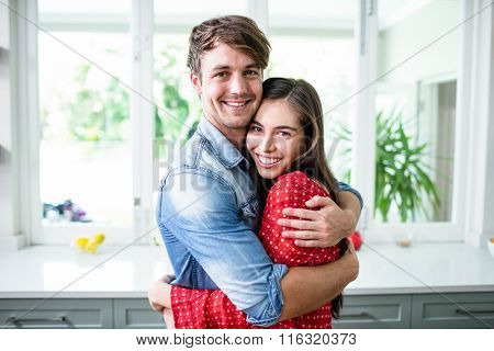 Happy couple hugging and looking at camera in the kitchen
