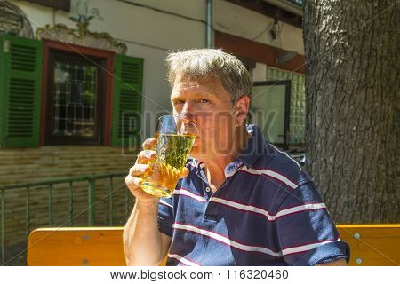 Thirsty Man Drinks Out Of A Glass In The Outdoor Garden