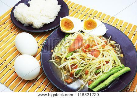 Thai Som Tum / Papaya Salad / Papaya Pok Pok with salted eggs and sticky rice on orange bamboo mat.