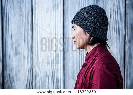 Side view of thoughtful hipster businessman on wooden background