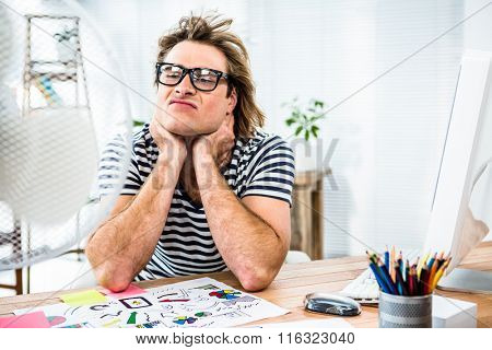 Hipster businessman sitting in front of fan and grimacing in his office