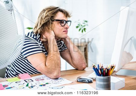 Troubled hipster businessman sitting in his office and holding his neck