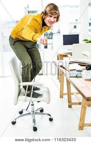 Happy hipster businessman standing on his chair in his office