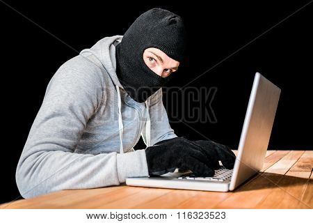 Focused thief with hood typing on laptop with black background