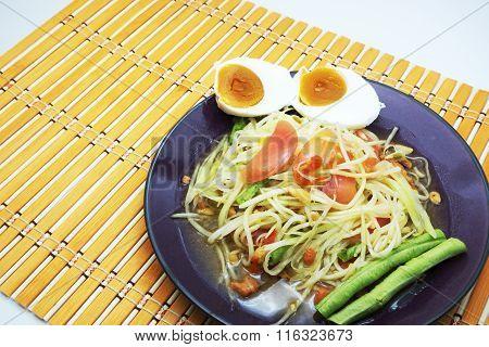 Thai Som Tum / Papaya Salad / Papaya Pok Pok with salted egg on orange bamboo mat.
