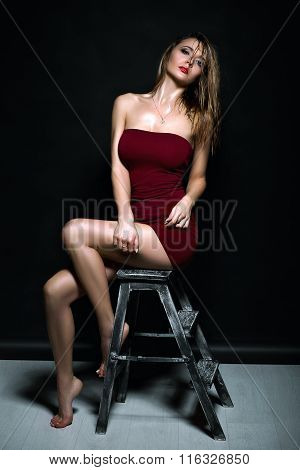 Sexy girl sitting on a chair in the studio