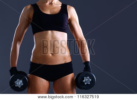 Athletic woman pumping up muscules with dumbbells