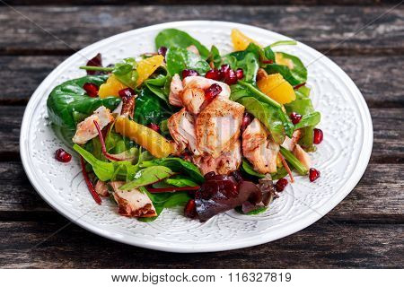 Fresh Salmon Salad with vegetables, pomegranate and orange.