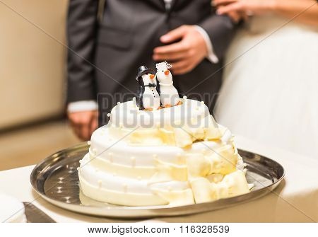 wedding cake with figurines of penguins at the top