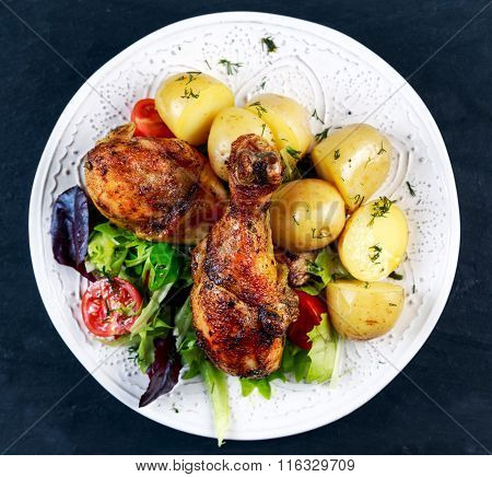 Baked chicken legs with potatoes and vegetables