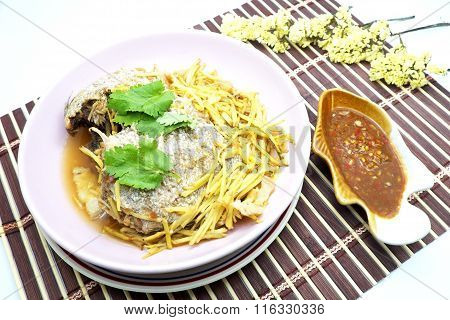 Steamed fish with ginger and spicy salted soy bean sauce in fish shaped bowl on brown bamboo mat.