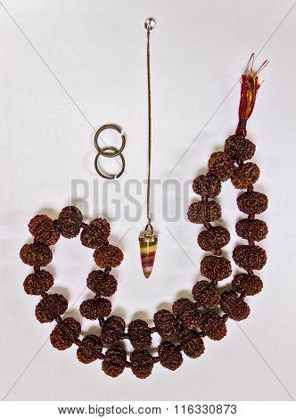 Spiritual tools on display ~ Rudraksha, two horse shoe rings & dowsing pendulum