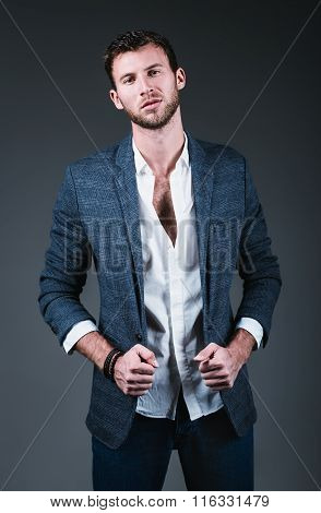 Studio Fashion Shot: Portrait Of Handsome Young Man Wearing Jeans, Shirt And Jacket