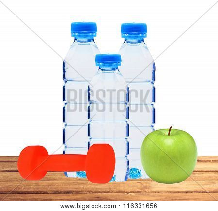 Blue Bottles With Water, Dumbell And Green Apple On Table Isolated On White