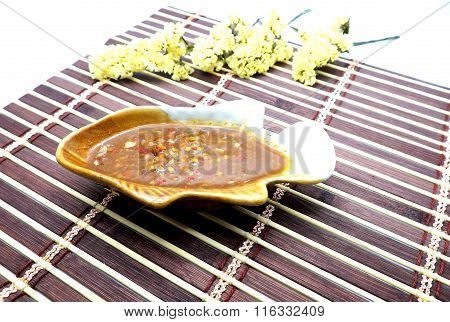 Spicy salted  soy bean sauce in fish shaped bowl on brown bamboo mat. Focus on surface of sauce.
