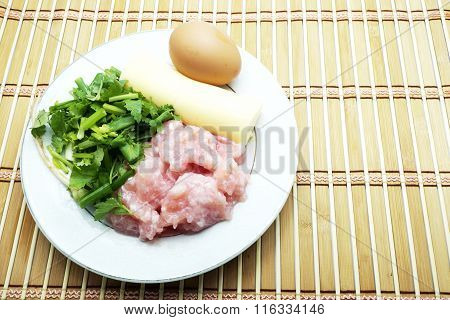 Raw material for clear soup with bean curd and minced pork with egg on brown bamboo mat.
